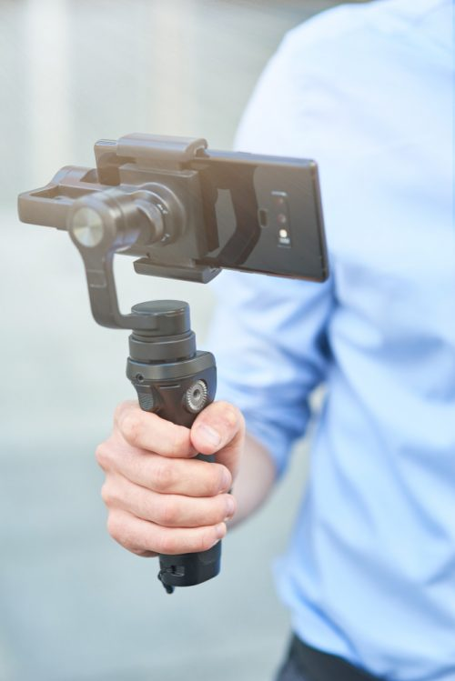 cropped-shot-male-blogger-holding-gimbal-with-smartphone-while-standing-outdoors-recording